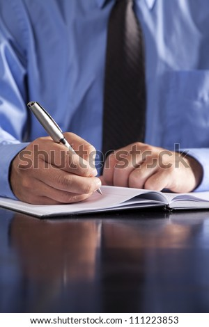 A young businessman writes in a notebook while sitting at a desk.