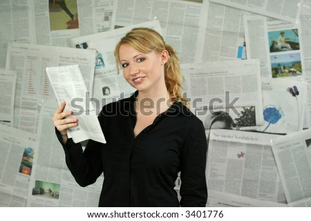 a young businesswoman against a wall with a lot of newspapers is reading