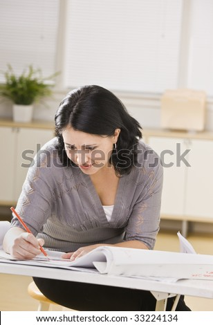 A young businesswoman is working on blueprints in an office.  She is looking away from the camera.  Vertically framed shot.