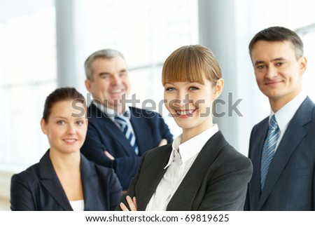 A young businesswoman smiling against her three partners