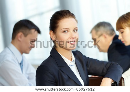 A young businesswoman smiling against working colleagues