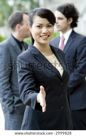 A young businesswoman stretches out her hand as if to welcome (shallow depth of field used)