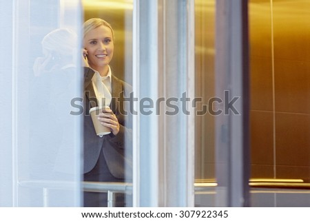 A young businesswoman talking on the phone in elevator
