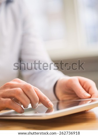 A young businesswoman uses a tablet computer over a wooden table or desk. #262736918
