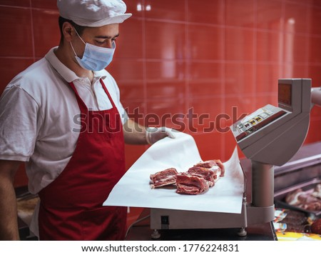 a young butcher measuring meat on an electric scale Foto stock ©