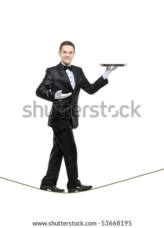 A young butler carrying a tray and walking on a rope isolated on white background