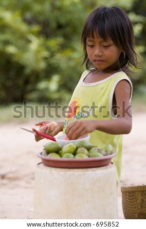 A young cambodian girl selling small melons - stock photo