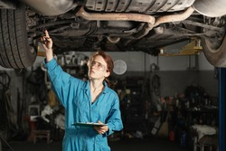 A young car mechanic girl examines the fastening of a wheel while standing under a car in a car repair shop or garage. Repair of the machine lifted up. Man's work and woman. The car is being diagnosed