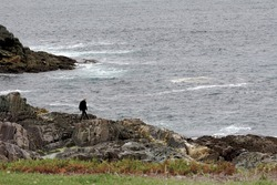A young carefully maneuvers around the rocky coastline of Newfounland and Labrador while enjoying the rugged coastline