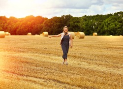 A young Caucasian blond woman with a smile walks along a mown wheat field where there are many round large sheaves of hay. Agriculture. Sheaves. Travel and vacation concept.