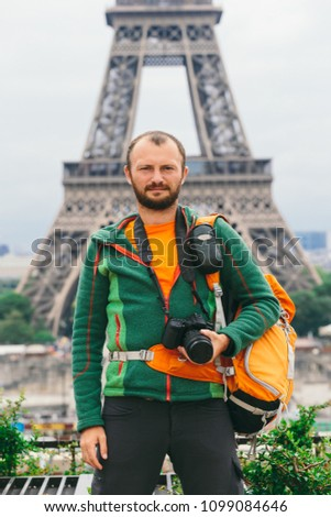 A young Caucasian Caucasian man with an orange backpack and a photo camera in his hands is standing in France, paris against the background of the Eiffel Tower. #1099084646