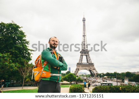 A young Caucasian Caucasian man with an orange backpack and a photo camera in his hands is standing in France, paris against the background of the Eiffel Tower. #1371235151