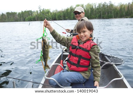 A young caucasian fisherman proudly holds up his first walleye of the day