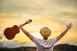 A young Caucasian man turned his back with a straw hat and a white T-shirt, greets the setting sun over the hills with open arms and holds a classical guitar in his hand.