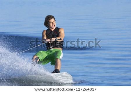 A young caucasian man wake boarding on lake