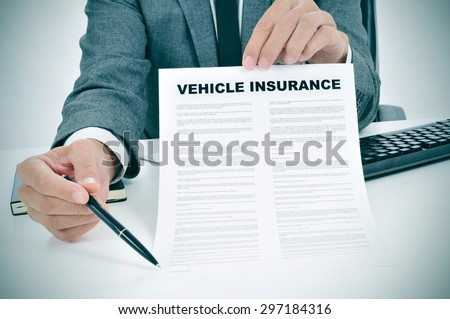 a young caucasian man wearing a gray suit in his office shows a vehicle insurance policy and points with a pen where the policyholder must to sign #297184316