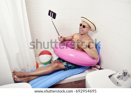 a young caucasian man wearing sunglasses, a straw hat and a pink swim ring in a blue air mattress placed in the shower of a bathroom takes a selfie with his smartphone while is drinking a red cocktail
