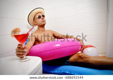 a young caucasian man wearing sunglasses, a straw hat and a pink swim ring pretending he is relaxing in a blue air mattress placed in the shower of a bathroom while is drinking a red cocktail