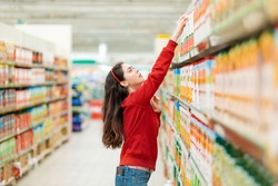 A young Caucasian woman in a red sweater reaches for a juice box on the top shelf. In the background, blurred rows of store shelves. The concept of buying products in a supermarket