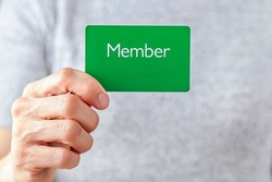A young caucasian woman is holding a green card that says member on it. A customizable image which has space for text to be inserted. Being a member, membership dues, subscription, group concepts.