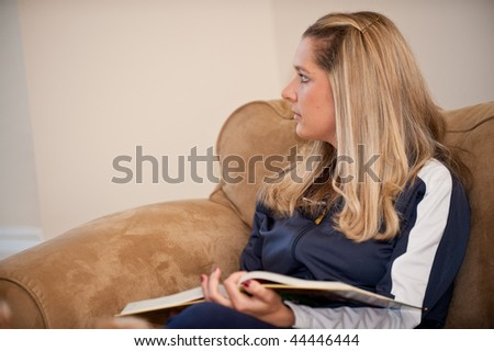 A young Caucasian woman relaxing on a couch with her dog and book