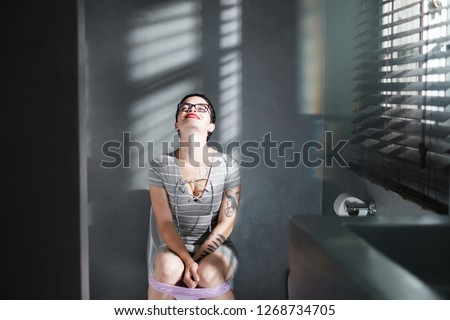 A young caucasian woman smiles with relief and satisfaction after being able to empty her bladder in the toilett. Attractive short haired woman sitting on toilett smiling with her underwear down