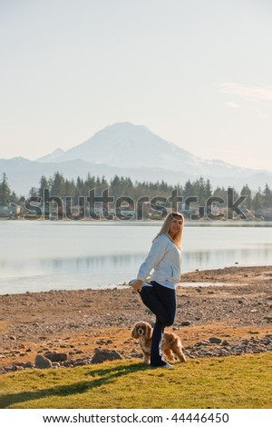 A young Caucasian woman stretching by a lake with her dog - stock photo