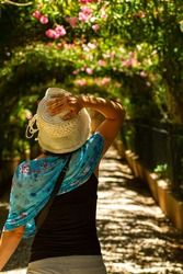 A young caucasian woman wearing a wide brim bucket hat made of loose knit raffia is walking alone in a garden trail inside Alhambra palace with beautiful floral arches creating shade in sunny summer.