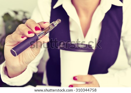 a young caucasian woman, with a cup of coffee in her hand, vapes from an electronic cigarette