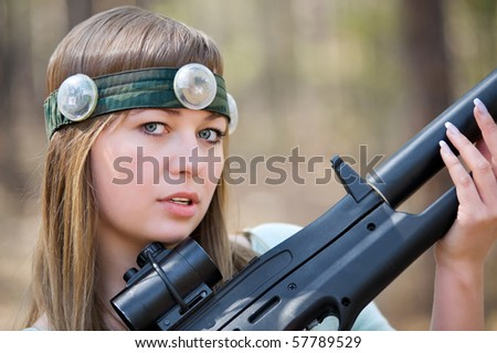 a young caucasian woman with a gun for a laser war game