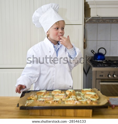 A young chef licking his fingers, enjoying the toppings he just used to garnish the bread he baked