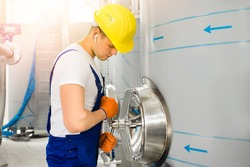 A young chemical plant worker tightens a threaded valve by opening a hatch in a large metal tank.