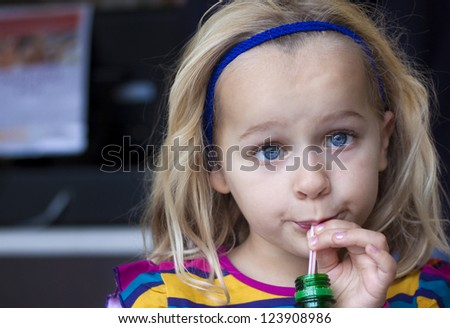 A young child drinking from a bottle with a straw