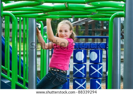 A young child having fun playing on equipment at a playground.