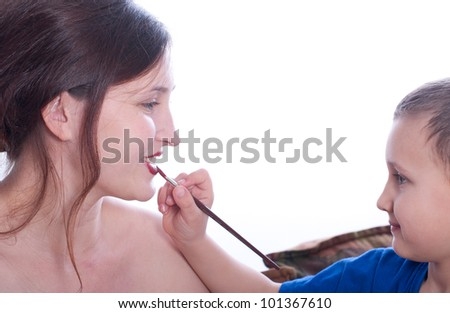 a young child helps her mother to apply makeup