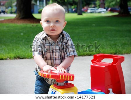 A young child holding onto the steering wheel of a toy truck, smiling. - horizontally framed