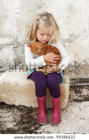A young child hugging a small kitten, very tender moment, lots of love