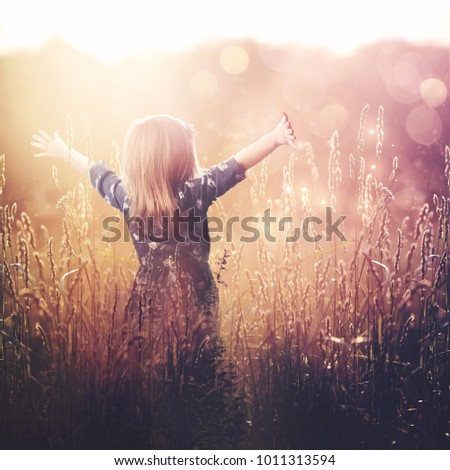 A young child is lifting her arms up in praise