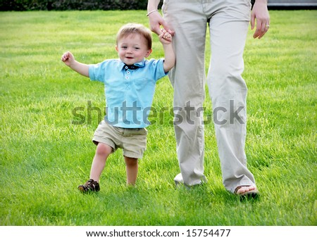 A young child is standing on the grass.  The mother is helping the child walk.  The baby is smiling and looking away from the camera.  Horizontally framed shot.