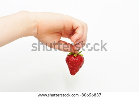 A young child picking up strawberry in hand.