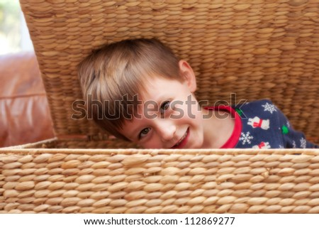 A young child playing hide and seek in a wicker container