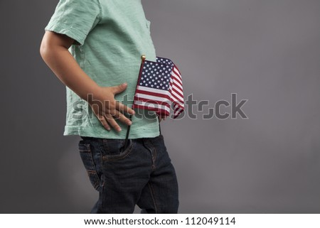 A young child plays with two American Flags.