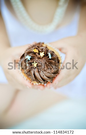 A young child's hands holding chocolate cupcake