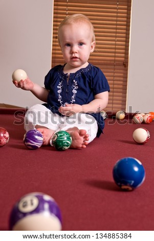 A young child sitting alone on a billiard table playing with the pool balls. She holds a cue ball in here hand and looks at the camera.