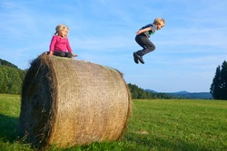 A young children boy and girl (siblings) playing on hay bale summertime. Children summer outdoor activities. Jumping high and far. Concept of summer vacation activity. Happy siblings playing on meadow