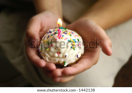 A young childs hands holding a special birthday cupcake.