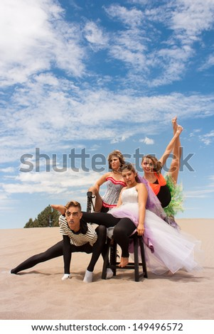 A young circus troupe pose supporting one another in the desert sand