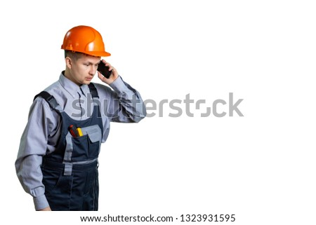 A young civil engineer in a helmet and workwear gets over the phone incredible information on repair and construction. isolated #1323931595