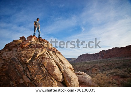 A young climber stands on a boulder looking out over the landscape of Red Rocks State Park west of Las Vegas, Nevada. - stock photo