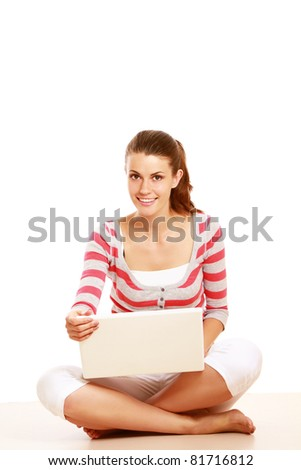 A young colledge girl sitting on the floor with a laptop, isolated on white